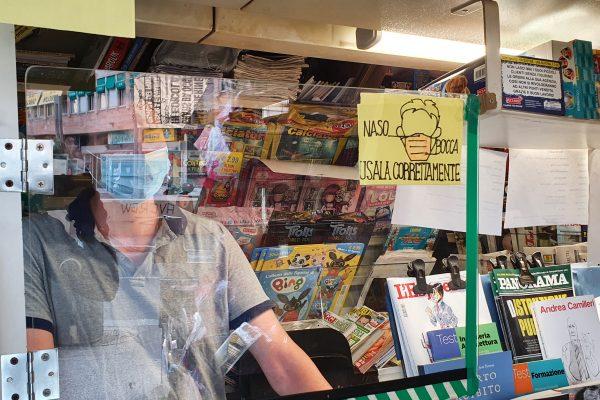 Luschi mostra i numerosi cartelli presenti all'interno della sua edicola dove è scritto di indossare la mascherina su naso e bocca